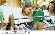 Купить «Portrait of smiling women choosing green sweater in the modern shop», видеоролик № 28303319, снято 27 марта 2018 г. (c) Яков Филимонов / Фотобанк Лори
