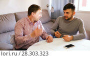 Купить «Two cheerful men enjoying conversation at home table», видеоролик № 28303323, снято 26 февраля 2018 г. (c) Яков Филимонов / Фотобанк Лори