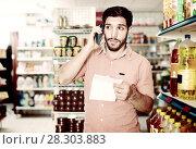 Купить «Portrait of adult male with note and smartphone in market.», фото № 28303883, снято 15 сентября 2017 г. (c) Яков Филимонов / Фотобанк Лори