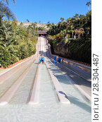 Купить «Семейный аттракцион Naga Racer - параллельные водные горки для спуска на коврике. Аквапарк Сиам, Коста-Адехе, Тенерифе, Канары, Испания», фото № 28304487, снято 29 декабря 2015 г. (c) Кекяляйнен Андрей / Фотобанк Лори