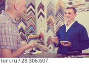 Купить «portrait of man seller taking order on picture frame from custom», фото № 28306607, снято 21 октября 2018 г. (c) Яков Филимонов / Фотобанк Лори