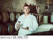 Купить «Young sommelier holding glass of wine and checking quality», фото № 28306731, снято 22 сентября 2016 г. (c) Яков Филимонов / Фотобанк Лори