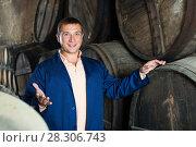 Купить «Man checking ageing barrel process», фото № 28306743, снято 22 сентября 2016 г. (c) Яков Филимонов / Фотобанк Лори