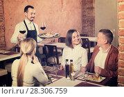 Купить «Young waiter placing order in front of guests», фото № 28306759, снято 20 апреля 2018 г. (c) Яков Филимонов / Фотобанк Лори