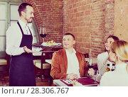 Купить «Male waiter bringing order to visitors», фото № 28306767, снято 22 июля 2018 г. (c) Яков Филимонов / Фотобанк Лори