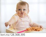 Купить «Adorable little baby one year eating pasta indoor. Funny toddler child with spaghetti. Cute kid and healthy food.», фото № 28308395, снято 27 февраля 2020 г. (c) Оксана Кузьмина / Фотобанк Лори
