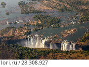Купить «Victoria Falls, the largest curtain of water in the world. The falls and the surrounding area is the National Parks and World Heritage Site, Zambia and Zimbabwe.», фото № 28308927, снято 25 марта 2019 г. (c) BE&W Photo / Фотобанк Лори