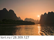 Купить «Scenic sunset over Karst mountains formations in Guilin, one of China most popular tourist destinations», фото № 28309127, снято 6 июля 2020 г. (c) BE&W Photo / Фотобанк Лори