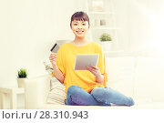 Купить «happy asian woman with tablet pc and credit card», фото № 28310943, снято 9 марта 2016 г. (c) Syda Productions / Фотобанк Лори