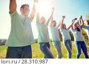 Купить «group of happy volunteers holding hands outdoors», фото № 28310987, снято 7 мая 2016 г. (c) Syda Productions / Фотобанк Лори