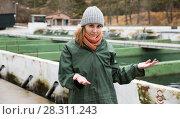 Купить «Female showing fish tanks on sturgeon farm», фото № 28311243, снято 4 февраля 2018 г. (c) Яков Филимонов / Фотобанк Лори