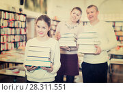 Купить «Cheerful preteen girl and her parents holding piles of books bought in bookstore», фото № 28311551, снято 22 февраля 2018 г. (c) Яков Филимонов / Фотобанк Лори
