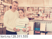 Купить «Girl with father standing with books in bookshop», фото № 28311555, снято 22 февраля 2018 г. (c) Яков Филимонов / Фотобанк Лори