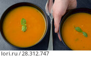 Купить «hands putting bowl of pumpkin cream soup on table», видеоролик № 28312747, снято 10 апреля 2018 г. (c) Syda Productions / Фотобанк Лори