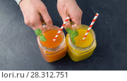 Купить «hands putting fresh juices in mason jars on table», видеоролик № 28312751, снято 8 апреля 2018 г. (c) Syda Productions / Фотобанк Лори