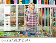 Купить «portrait of female cashier standing at cash desk in embroidery shop», фото № 28312847, снято 15 декабря 2018 г. (c) Яков Филимонов / Фотобанк Лори