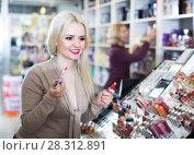 Купить «Young woman choosing lip plumper», фото № 28312891, снято 16 июля 2018 г. (c) Яков Филимонов / Фотобанк Лори