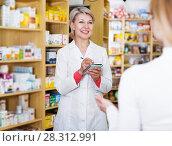 Купить «Seller helping customer to choose care products», фото № 28312991, снято 15 марта 2017 г. (c) Яков Филимонов / Фотобанк Лори