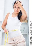Купить «Young sad woman measures waist», фото № 28313027, снято 20 марта 2019 г. (c) Яков Филимонов / Фотобанк Лори
