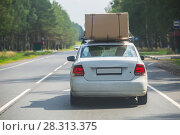 Купить «Car with cardboard box on the upper trunk is moving along the highway», фото № 28313375, снято 27 июля 2017 г. (c) Юрий Бизгаймер / Фотобанк Лори