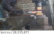 Купить «Blacksmith forging red hot iron on anvil - automatic hammering», фото № 28315871, снято 17 июля 2018 г. (c) Константин Шишкин / Фотобанк Лори