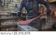 Купить «The blacksmith manually forging in the smithy», фото № 28315879, снято 17 июля 2018 г. (c) Константин Шишкин / Фотобанк Лори