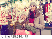Купить «Smiling female and her daughter are choosing decorations for Christmas tree in the market outdoor.», фото № 28316479, снято 19 декабря 2017 г. (c) Яков Филимонов / Фотобанк Лори