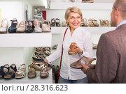 Купить «Mature woman picking shoes in boutique», фото № 28316623, снято 27 мая 2020 г. (c) Яков Филимонов / Фотобанк Лори