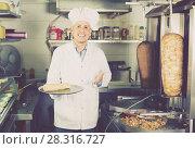Купить «Mature man chef holding plate with delicious kebab», фото № 28316727, снято 15 октября 2018 г. (c) Яков Филимонов / Фотобанк Лори
