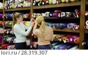 Купить «Two cheerful young female friends looking for interesting cloth in textile shop», видеоролик № 28319307, снято 28 марта 2018 г. (c) Яков Филимонов / Фотобанк Лори