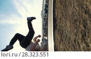 Купить «Urban acrobatics - teenager performing somersault outdoor», видеоролик № 28323551, снято 25 апреля 2018 г. (c) Константин Шишкин / Фотобанк Лори