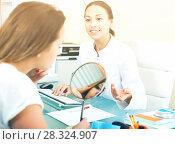 Купить «Woman client checking result of beauty procedures», фото № 28324907, снято 21 февраля 2019 г. (c) Яков Филимонов / Фотобанк Лори