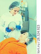 Купить «Woman client checking result of beauty procedures», фото № 28324923, снято 21 февраля 2019 г. (c) Яков Филимонов / Фотобанк Лори