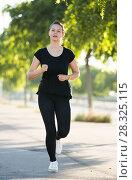 Купить «Young woman running along city streets», фото № 28325115, снято 5 июля 2017 г. (c) Яков Филимонов / Фотобанк Лори