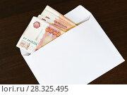 Купить «Белый конверт с пачкой пятитысячных рублевых купюр лежит на темном столе», фото № 28325495, снято 23 марта 2017 г. (c) Наталья Гармашева / Фотобанк Лори