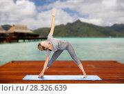 Купить «woman making yoga triangle pose on mat outdoors», фото № 28326639, снято 13 ноября 2015 г. (c) Syda Productions / Фотобанк Лори