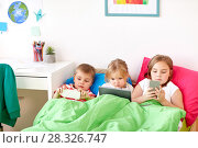 Купить «kids with tablet pc and smartphones in bed at home», фото № 28326747, снято 15 октября 2017 г. (c) Syda Productions / Фотобанк Лори