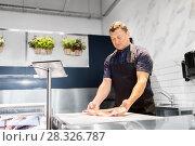 Купить «seller weighing fish on scale at seafood shop», фото № 28326787, снято 28 февраля 2018 г. (c) Syda Productions / Фотобанк Лори
