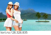 Купить «smiling young women in hats on bora bora beach», фото № 28326835, снято 11 июля 2013 г. (c) Syda Productions / Фотобанк Лори
