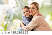 happy mother hugging daughter over cherry blossom. Стоковое фото, фотограф Syda Productions / Фотобанк Лори