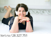 Купить «woman listens to music on headphones and lies on bed», фото № 28327751, снято 4 марта 2018 г. (c) Володина Ольга / Фотобанк Лори