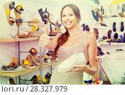 Купить «Positive young woman standing with chosen shoe», фото № 28327979, снято 15 ноября 2018 г. (c) Яков Филимонов / Фотобанк Лори