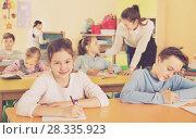 Купить «Teacher woman helping children during lesson in schoolroom», фото № 28335923, снято 28 января 2018 г. (c) Яков Филимонов / Фотобанк Лори