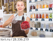 Купить «Young woman is offering dried flowers of Hibiscus in container», фото № 28336219, снято 4 сентября 2017 г. (c) Яков Филимонов / Фотобанк Лори