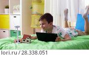 Купить «boy with tablet pc and wind turbine toy at home», видеоролик № 28338051, снято 20 апреля 2018 г. (c) Syda Productions / Фотобанк Лори