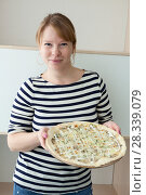 Купить «Женщина в полосатой футболке стоит с пиццей в руках», фото № 28339079, снято 15 апреля 2018 г. (c) Кекяляйнен Андрей / Фотобанк Лори