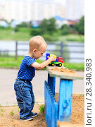 Купить «Little, two years old boy smiling playing in the sandbox using a excavator», фото № 28340983, снято 19 января 2019 г. (c) Mikhail Starodubov / Фотобанк Лори