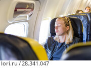 Купить «Tired blonde casual caucasian lady napping on seat while traveling by airplane.», фото № 28341047, снято 21 ноября 2019 г. (c) Matej Kastelic / Фотобанк Лори