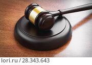 Купить «Judge's gavel on a wooden table», фото № 28343643, снято 12 апреля 2018 г. (c) Александр Лычагин / Фотобанк Лори