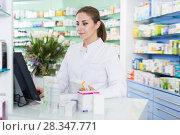 Купить «Young pharmacist is standing near cashbox», фото № 28347771, снято 26 марта 2018 г. (c) Яков Филимонов / Фотобанк Лори